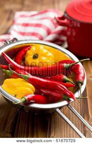 chili peppers and habanero in colander on wooden table