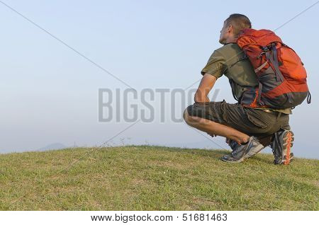 Male Hiker Resting On Hill Top