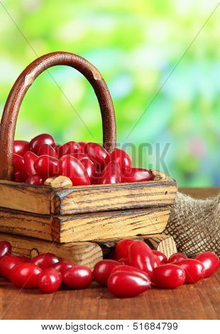 Fresh cornel berries in basket on wooden table