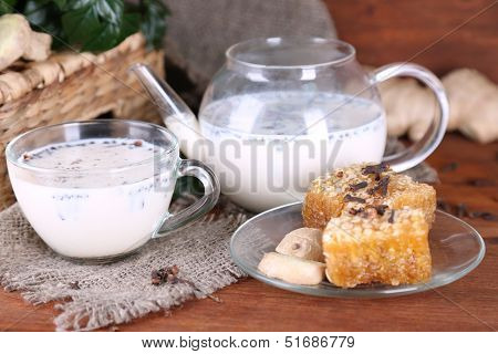 Teapot and cup of tea with milk and spices on sackcloth of wooden table on bright background