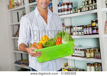 Midsection of mid adult man with basket of fresh vegetables standing in grocery store