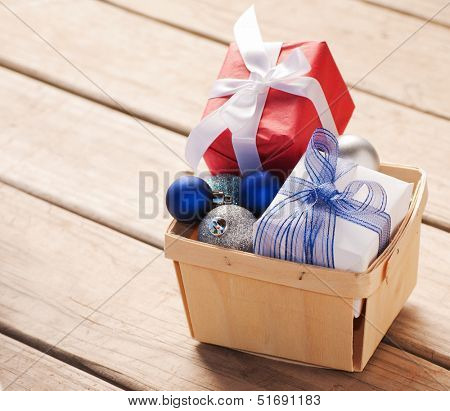 Christmas gifts and baubles in a wooden basket on rustic board background