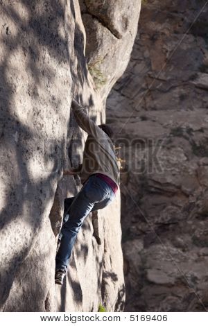 Young Man Climbing Beside Waterfall