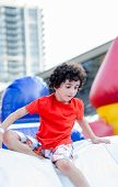 stock photo of inflatable slide  - Hispanic boy having fun and enjoying a day outdoor in an inflatable playground.