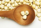 foto of tablespoon  - dry lotus seed in wooden tablespoon in white background on table - JPG