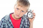 stock photo of time-piece  - Confused young kid holding time piece close to his ear - JPG