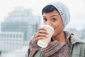 picture of beanie hat  - Happy young model in winter clothes enjoying coffee outside on a cloudy day - JPG