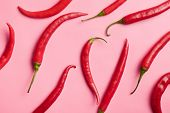 top view of chili peppers on pink background