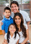 stock photo of toothless smile  - Portrait of a Latin family smiling at home looking very happy  - JPG