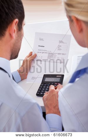 Collegues Checking An Invoice On A Calculator