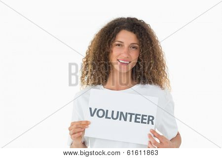 Happy volunteer showing a poster on white background
