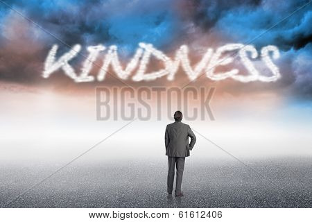 The word kindness and businessman with hand on hip against cloudy landscape background