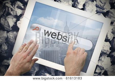 Hand touching the word website on search bar on tablet screen on crumpled papers