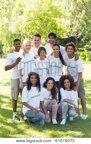Group portrait of confident multiethnic volunteers together in park