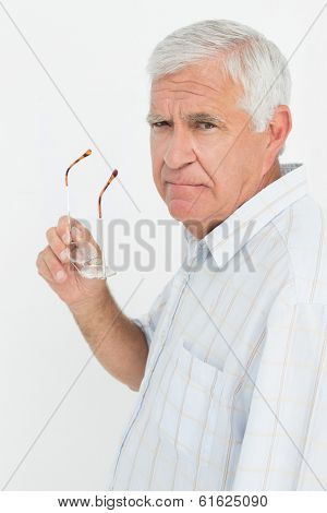 Portrait of a senior man holding glasses over white background