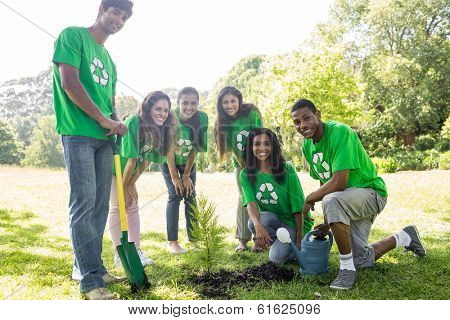 Group portrait of confident environmentalists gardening in park