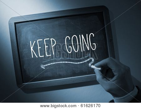 Hand writing the word keep going on black chalkboard