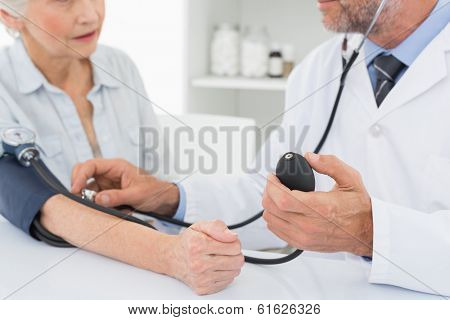 Mid section of a doctor taking the blood pressure of his retired patient in the medical office