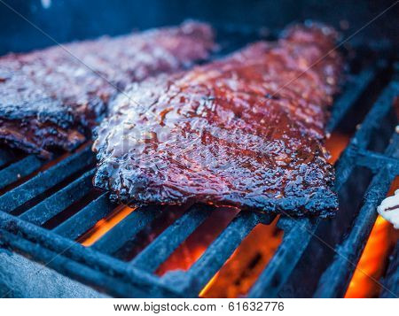 Ribs On The Grill With Fire On The Side And Smoke Comming Up