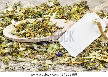 Curative natural herbal tea on wooden spoon with hang tag