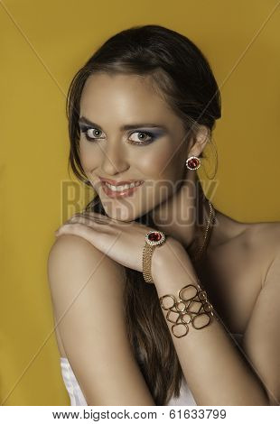Portrait of smiling brunette woman with gold jewelry