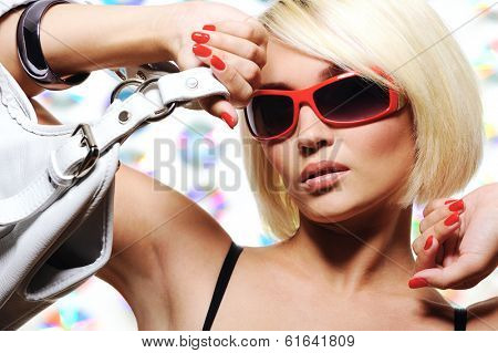 portrait of trendy woman with  red sunglasses holding white handbag