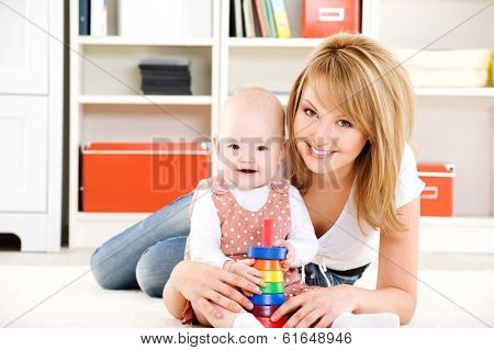 Beautiful baby playing with toys with happy mother  indoors