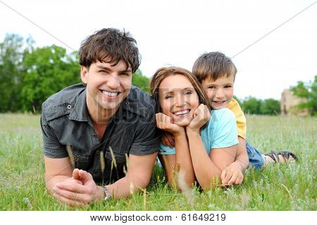 Happy beautiful young family lying on the  green grass. Three cheerful person