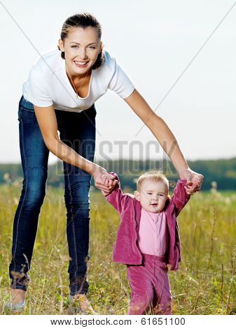 Happy young beautiful mather with smiling  baby  on nature