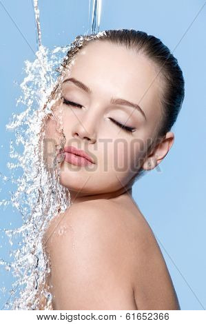 Young sensuality beautiful teen with clean skin with splash of water - blue background