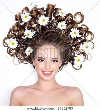 Smiling young woman with flowers in her  long curly hair - white background