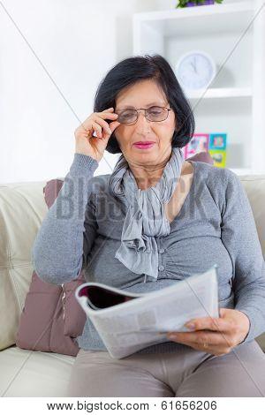 Grandmother enjoying a rest, reading magazine