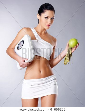 Healthy woman stands with the scales and green apple. Healthy eating concept.