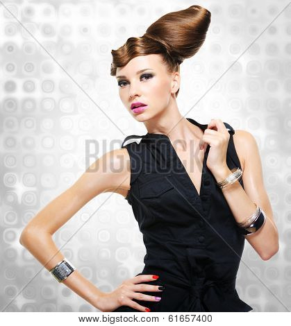 Beautiful woman dressed in black dress posing at studio