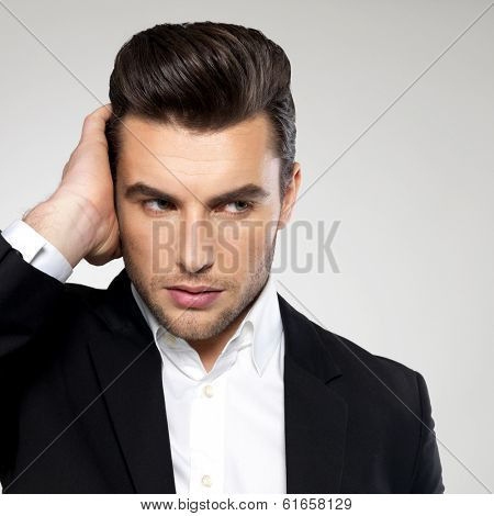 Closeup face of a fashion young businessman in black suit casual  poses at studio