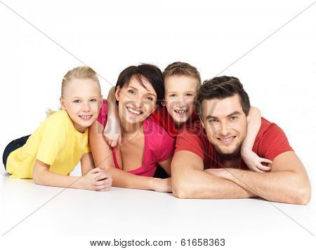 Portrait of the happy young family with two children lying at studio on white floor