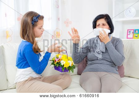 Cute girl giving a bunch of flowers to her grandmother.