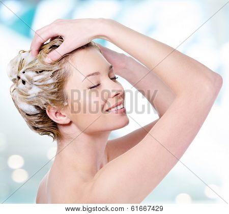 Beautiful young blond woman with attractive smile soaping her head - isolated on white background
