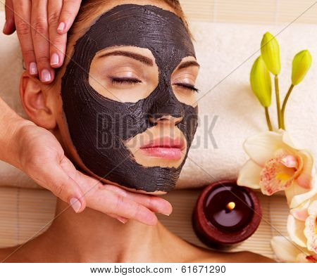 Cosmetologist doing massage on the woman's face  in sap salon. Female with scrub cosmetic mask on face.
