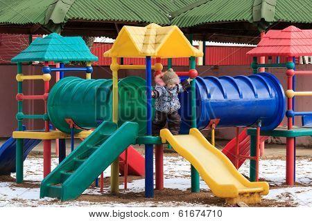 Beautiful happy kid on winter playground outdoor