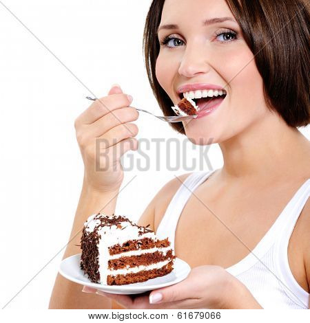 Pretty young woman eats a sweet cake  isolated on white