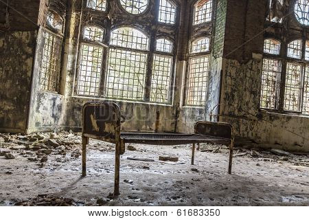 Old Rusty Bed In Ruinous House In Front Of Some Windows
