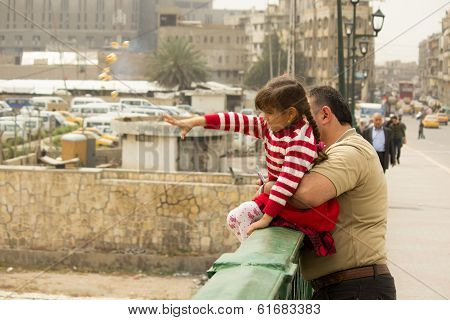 Iraqi man with his child feeding seagulls