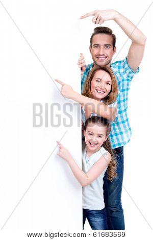 Portrait of an american family pointing by finger to the banner - isolated on a white background