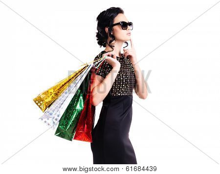 Portrait of thinking elegant woman in black dress and glasses with shopping bags - isolated on white.