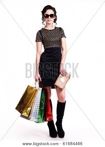 The beautiful fashionable young woman in black dress and glasses with purchases in hands - isolated on white.