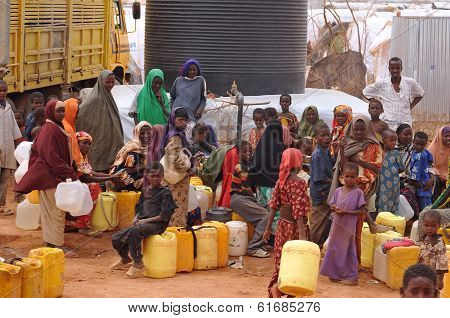 People Waiting To Fill Water And Mess