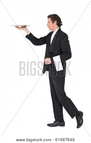 Full length of waiter in suit carrying tray isolated over white background