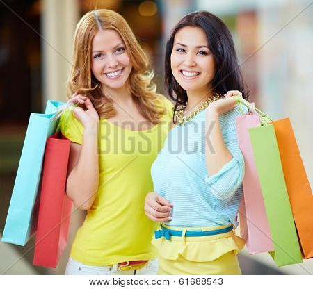 Portrait of two happy girls in smart casual holding paperbags