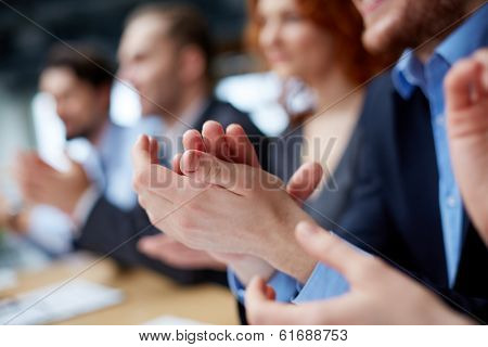 Photo of business partners�¢?? hands applauding at the meeting